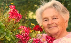 A senior woman standing by flowers